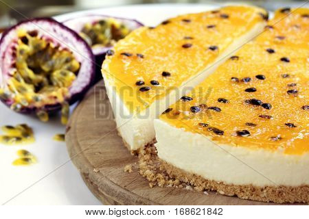 Passionfruit cheesecake, side view on old board.  Focus on front of cheesecake.  Fresh fruit behind.