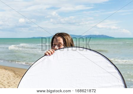 Girl Holding A Photo Reflector At The Beach