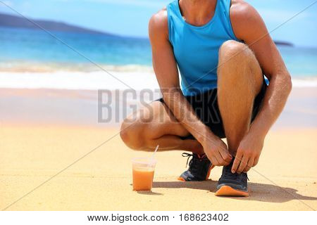 Running shoes and healthy fruit juice smoothie. closeup of man tying shoe laces. Sport fitness athlete runner getting ready for jogging on beach with morning juicing drink.