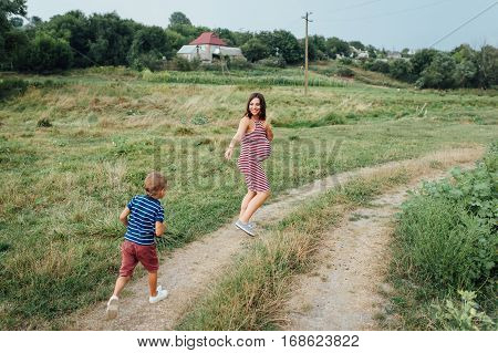 Pregnant Woman Walking Countryside With Her Son.