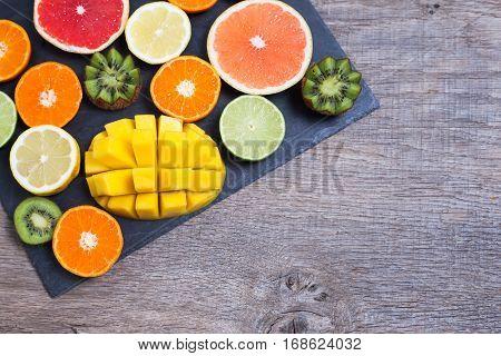 Raw fruit rich in vitamin C on the black slate platter: oranges grapefruits lemons limes kiwis slices