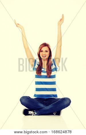 Happy teenage woman sitting with arms up