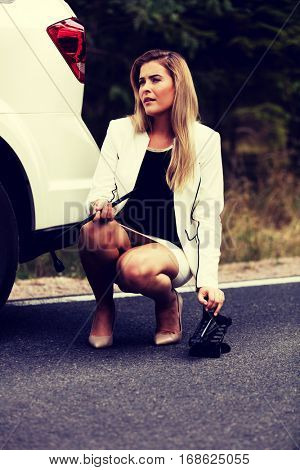 Young woman holding jacke and wheel wrench