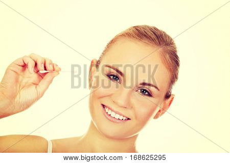 Young happy woman cleans her ear