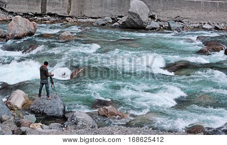 Aadventurous Photographer on dangerous flooded river in Azad Kashmir. standing on a rock and capturing the moment with his camera on tripod.