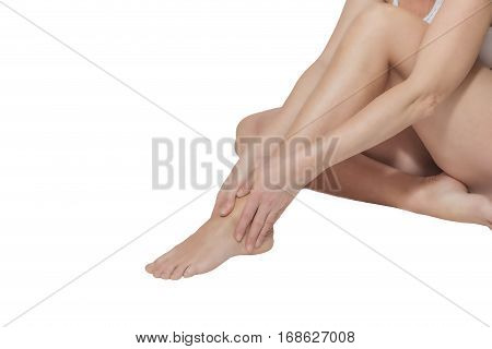 Side view of middle age woman sitting on a white background and holding by both hands her ankle