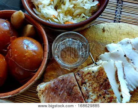 Homemade lard with condiments. Glass of vodka, sauerkraut, pickled tomatoes. Natural food, appetizer. Closeup. Traditional Dishes of Russian Cuisine
