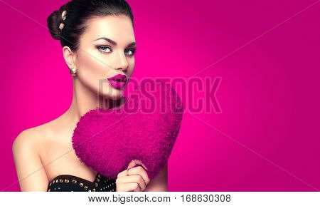 Sexy Valentine model Girl portrait. Gorgeous Valentines young brunette woman with heart shaped Purple pillow on pink background. Perfect make up. Valentine' Day brunette lady headshot.