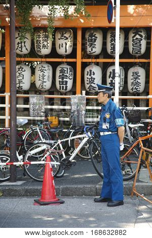 TOKYO-JAPAN, 27 June 2016: Japanese police man standing in front of japanese lantern at tsukiji fish market in Tokyo, japan. The biggest wholesale fish and seafood market in the world.