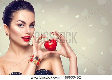 Fashion woman with red heart. Valentine's day art portrait. Beautiful make up and manicure. Surprised model girl face. Gorgeous glamour lady with bright makeup. Showing Heart Sign gesture.