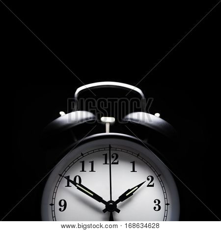 Alarm clock in the middle of the night isolated on black concept for insomnia or sleepless night