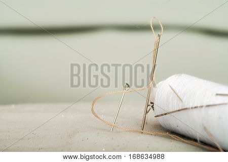 Sewing textile or cloth. Work table of a tailor. Detail of a needle with thread in the workroom reel of thread and natural fabric. . Shallow depth of field. Focus on needle.