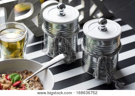 Metal containers for coffee and sugar stylishly decorated in Shabby chick style next to oatmeal and green tea