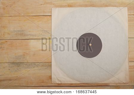 Retro styled image of a collection of old vinyl record lp's with sleeves on a wooden background. Copy space. Top view.