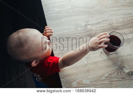 The child tries to get a drink from the table in a red shirt red for the drink