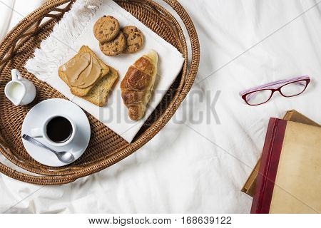 Breakfast Tray in Bad, Lifestyle / Tray with coffee, croissant, toast, peanut butter and cookies in bad, top view