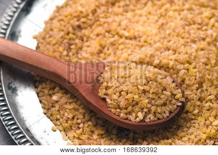 Placer grain bulgur on a tin plate and spoon partial blur horizontal