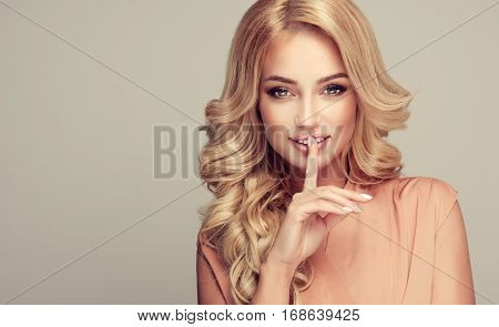Beautiful girl blonde hair with an elegant hairstyle holding a finger to her mouth with a secret .Woman with hair wavy ,curly hairstyle .