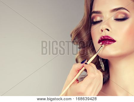 Hand of make-up master, painting lips of young beautiful model. Makeup in progress.