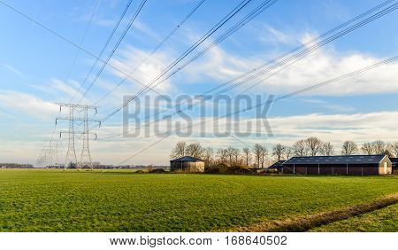 Power pylons and high voltage lines in an agricultural landscape in the Netherlands. In the background are the outbuildings of a farm. It is a cloudy day in the winter season.