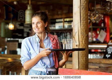 Happy Waitress Standing At The Bar Holding Drinks