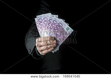 Businessman holding a fistful of 500 euro banknotes extended to the camera conceptual of wealth success or payoff cropped closeup over black background.
