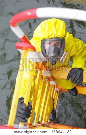 overhead view of specialist in protective suit and mask on ladder above water