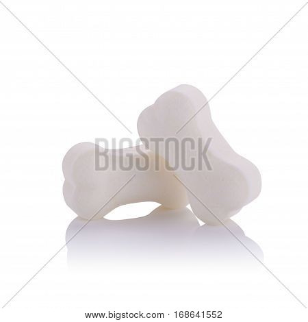 Milk pellet in the shape of a bone on white background