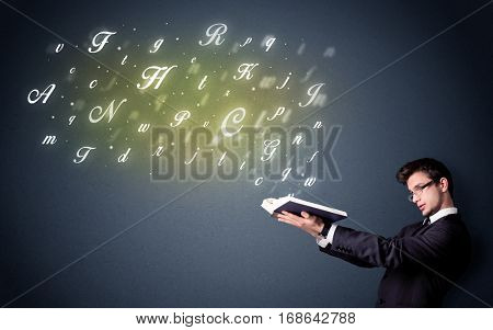Casual young man holding book with shiny letters flying out of it