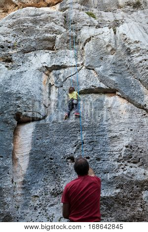 Little girl climbing on a limestone wall, rock on the background