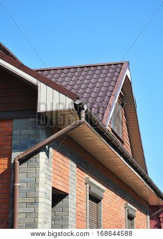 Rain gutter pipes and downspout system against attic roofing.