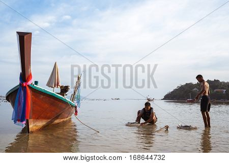 THAILAND PHUKET ASIA - JANUARY 31 2017: Thai children schoolchildren playing on the beach in the bay with the old Fishing boats at low tide.
