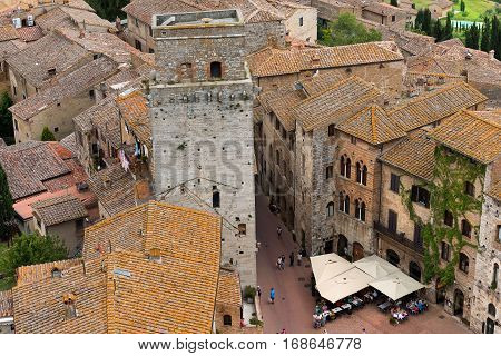 SAN GIMIGNANO ITALY - JULY 12 2014: Tourists visit the ancient and medieval Cisterna square (piazza della cisterna). San Gimignano (UNESCO heritage) Siena Tuscany Italy