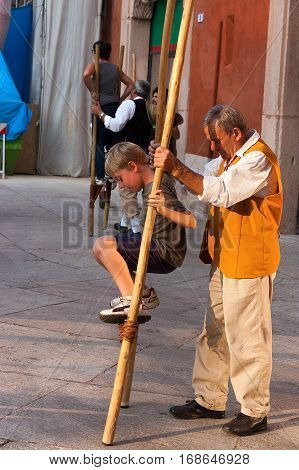VERONA ITALY - SEPTEMBER 24 2011: Tocati International festival of street games. An instructor of the Schieti village (Urbino Italy) teaches a young boy to stay balanced on wooden stilts
