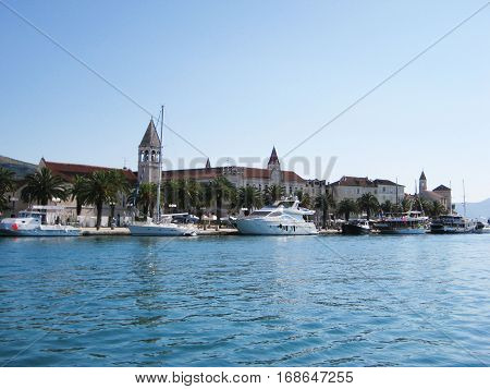Small tourist boats at luxury yacht club marina water front in historical european small town. Sunny summer day scene with blue clear sky and sea background. Recreation, relax, travel, vacation concept with empty copyspace