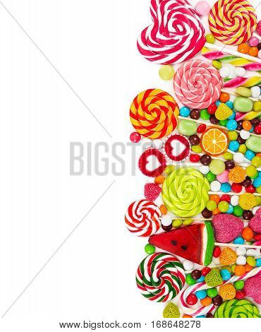 Colorful candies and lollipops isolated on white background. Top view.