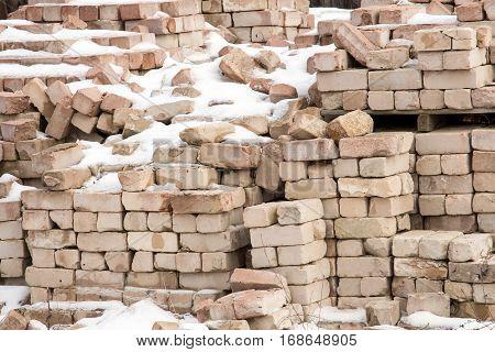 Pile of masonry bricks under the snow