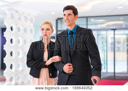 Man and woman arriving at hotel lobby with suitcase