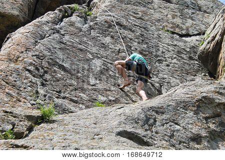 Boy rock climber climbs on the rock