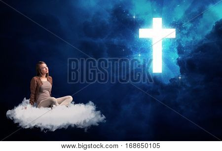 Caucasian woman sitting on a white fluffy cloud looking at a big, bright; blue; glowing cross poster