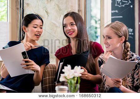 Three beautiful young women holding files while sitting in a coffee shop