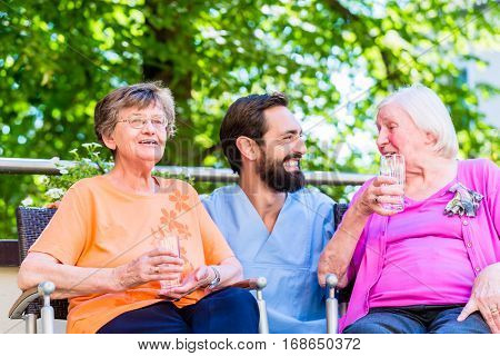 Nurse drinking coffee with seniors on terrace of retirement home