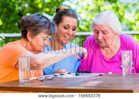 Two senior ladies playing board game in rest home