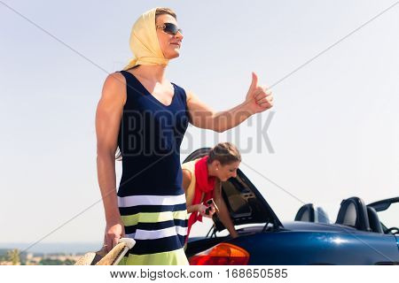 Two women having engine breakdown on summer joyride with convertible car