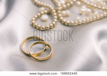 Golden wedding rings and pearl necklace over satin background