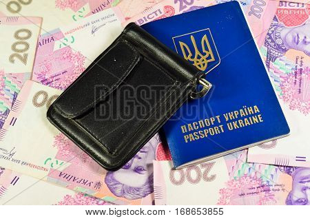 Black leather money clip and foreign passport on a background of the ukrainian banknotes