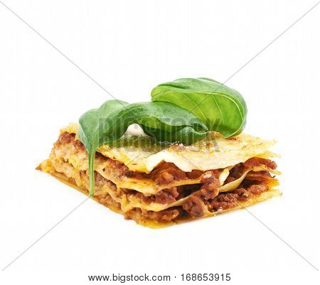 Single slice of lasagna with the fresh basil leaf over it, composition isolated on the white background