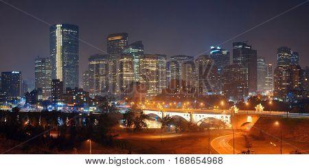 Calgary downtown cityscape with skyscraper and bridge at night, Canada.
