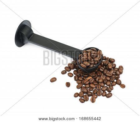 Pile of brown roasted coffee beans with the plastic tamper spoon over it, composition isolated over the white background