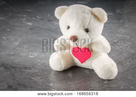 White teddy bear with love letter on red heart on gray background. Say i love you for valentine 's day concept.